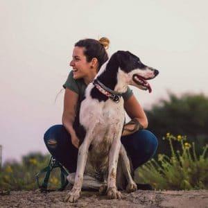 מאלפת כלבים יושבת ליד הכלב שלה בשדה