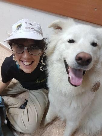 נערה מפרויקט גדולים במדים עם כלב לבן