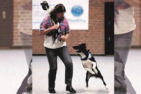 מדריכה עומדת עם כלב שקופץ כדי לתפוס את המשחק